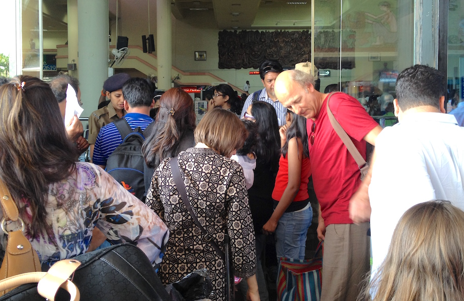 A large 10 to 15 people crowd round the entrance to the airport.