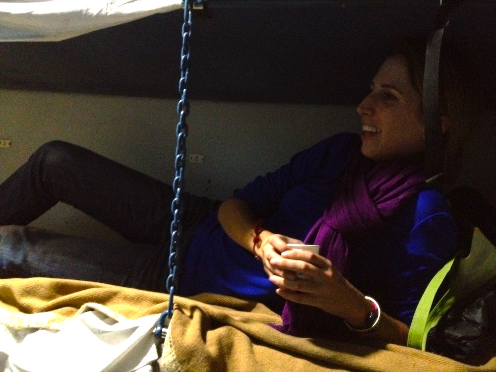 Young woman lounges on the middle bunk of a sleeper cabin in Indian train car.