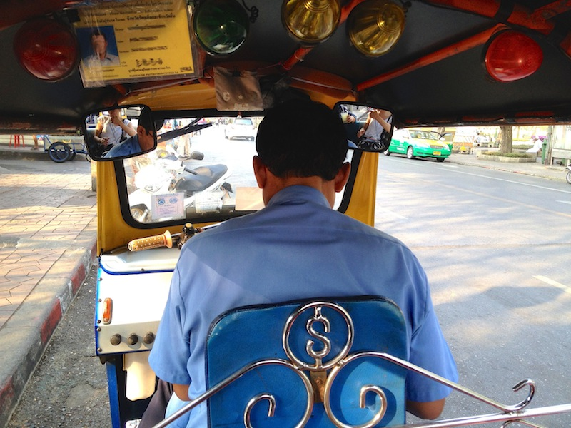 Back of driver from inside a Tuk tuk in Bangkok