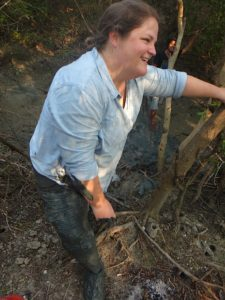 Writer climbing out of the banks of the gully with mud-covered pants