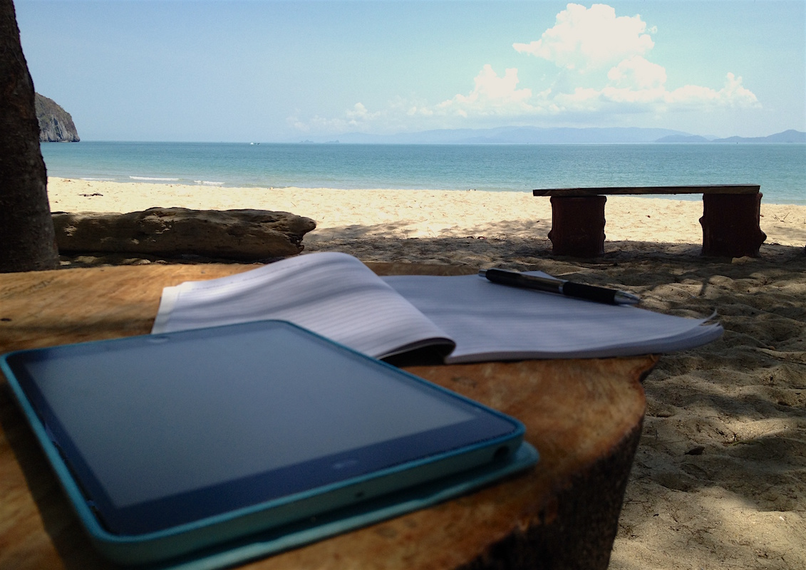 iPad and notebook on driftwood table on Thai beach